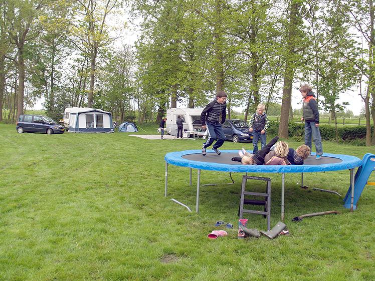 kamperen en trampoline springen op het veld voor de boerderij